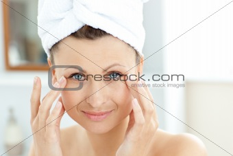 Cute young woman with a towel putting cream on her face in the b
