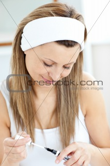 Glowing young woman using mascara in the bathroom