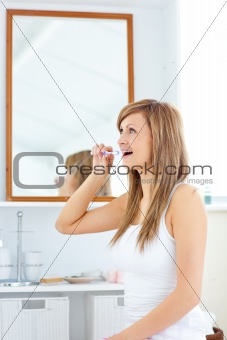 Blond young woman brushing her teeth standing in the bathroom