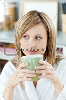 Charming caucasian blond woman enjoying her coffee in the kitche