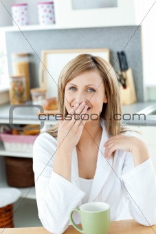 Caucasian blond woman enjoying her coffee in the kitchen