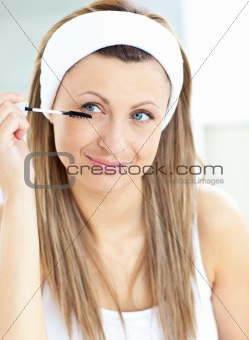 Caucasian woman using mascara in the bathroom