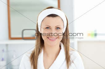 Charming young woman smiling at the camera in the bathroom
