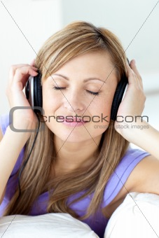 Positive caucasian woman listening to music with headphones in t