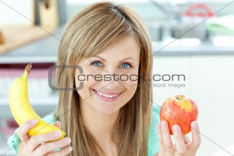 Positive caucasian woman holing a banana and an apple in the kit