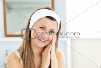 Charming young woman putting cream on her face in the bathroom
