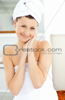 Attractive young woman with a towel putting cream on her face in
