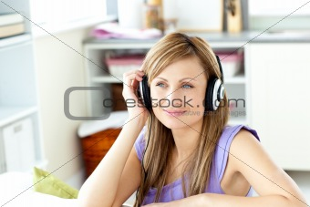 attentive woman sitting in the sofa listening to the music