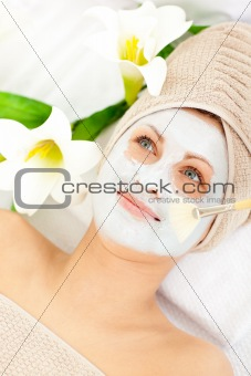 Captivating young woman receiving white cream on her face
