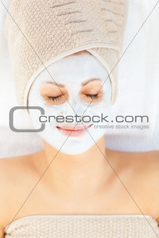 Cute young woman with closed eyes having white cream on her face