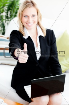 Postive businesswoman with thumb up using her laptop