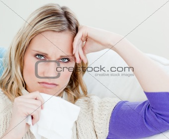 Unhappy sick woman holding tissues looking at the camera