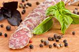 Slices of salami, basil and pepper