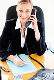 Self-assured businesswoman talking on phone and writing in her o