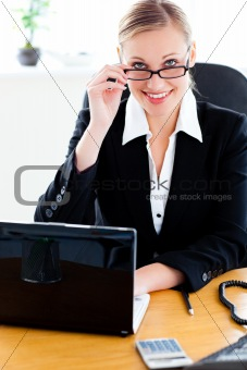 Charismatic businesswoman holding her glasses and using her lapt