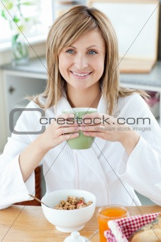 Beautiful woman holding a cup of coffee eating cereals in the ki