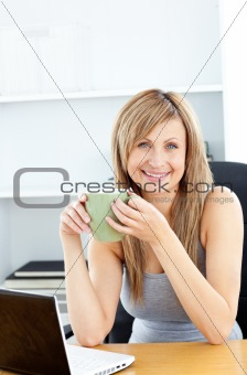 Attractive businesswoman holding a cup using her laptop