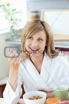 Bright woman eating cereals wearing a bath robe