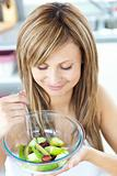 Pretty young woman eating a fruit salad in the kitchen