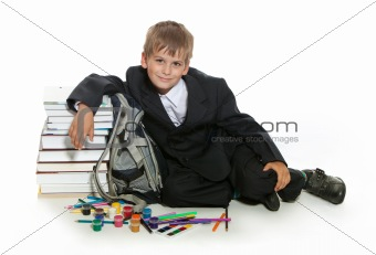 Boy, pencils, paints and books