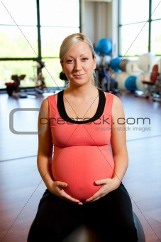 Pregnant woman sitting on fitness ball holding belly.