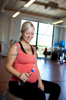 Pregnant woman relaxing with water bottle in hand.