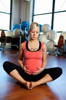 Pregnant woman relaxing and holding belly.