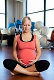 Pregnant woman holding her belly and relaxing.