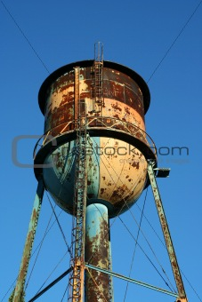 Old rusty watertower against blue sky