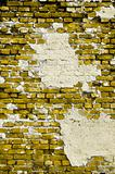 Old yellow wall with cracks and patches of plaster