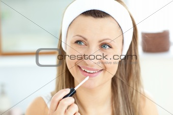 Attractive young woman using lipgloss in the bathroom