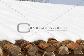 aged clay roof tiles snowed under winter snow