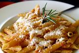 Penne pasta with cheese, served on a plate