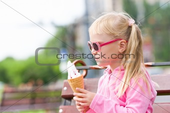 Little blond girl eating ice-cream