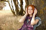 Young  smiling fashion with headphones near tree.
