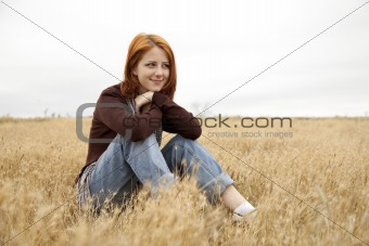 Beautiful red-haired girl sitting at yellow autumn grass.