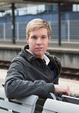 Young blond man in railway station