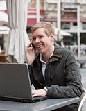 Young happy man with phone and laptop