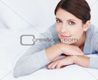 Pretty relaxed Caucasian woman lying on bed