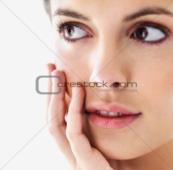Closeup beauty portrait of a charming girl with hand on cheek