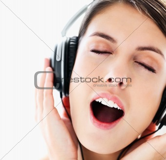 Closeup of an excited young girl listening to music eyes closed