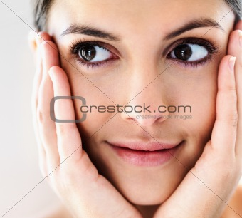 Closeup of a charming young girl holding her face with hands