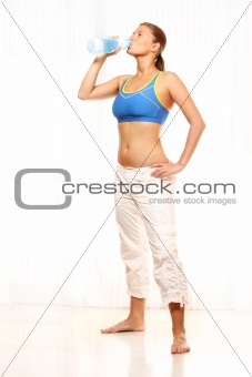 A fit woman drinking water