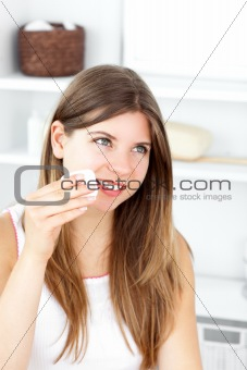 Beautiful woman putting make-up on her face in the bathroom