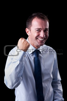 Portrait of a very happy  businessman with his arm raised, on black background. Studio shot