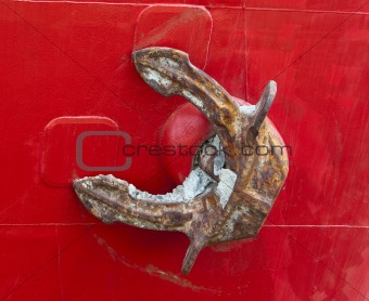 Old heavy rusty anchor on a red freighter's hull