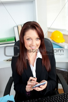 Positive businesswoman using her calculator sitting at her desk