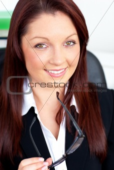 Charismatic businesswoman holding her glasses sitting in her office