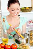 Charming woman cooking sphaghetti in the kitchen
