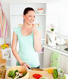 Radiant young woman tasting her salad at home
